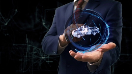 Businessman shows concept hologram 3d Pickup truck on his hand. Man in business suit with future technology screen and modern cosmic background