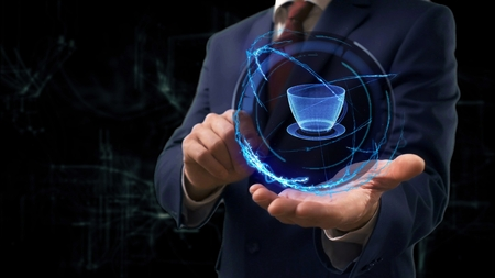 Businessman shows concept hologram 3d cup on his hand. Man in business suit with future technology screen and modern cosmic background