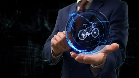 Businessman shows concept hologram 3d bike on his hand. Man in business suit with future technology screen and modern cosmic background