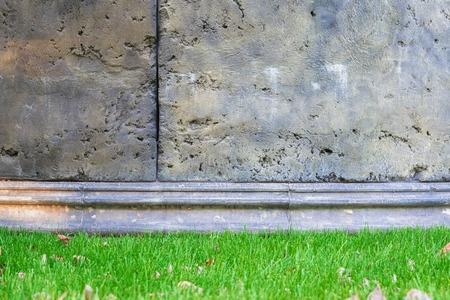 concrete: Interior de un antiguo castillo con un muro de hormigón y un césped verde.