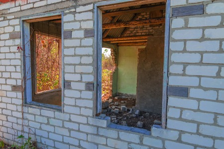 indigence: An old abandoned brick house with a broken window, closeup. As background for design of crisis. Stock Photo