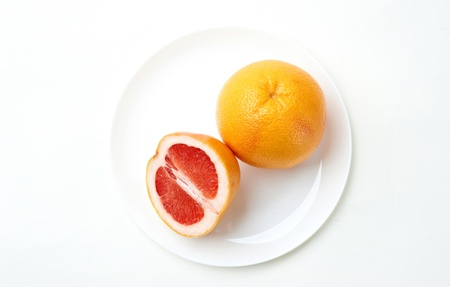 cut and whole grapefruits on a plate