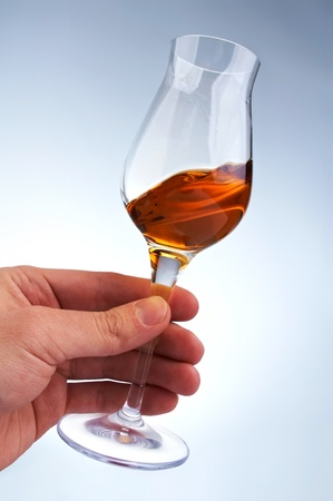 glass of brandy or whiskey swirling  in the hand Stock Photo