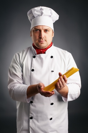 cook with spaghetti in his hands on grey background