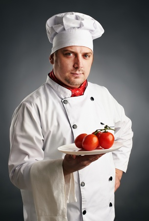 attractive chef in uniform with tomatos Stock Photo
