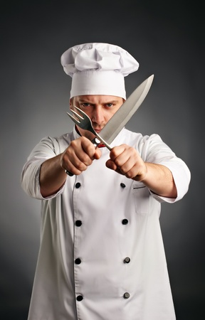 emotional cook with knife and fork in his hands on grey background