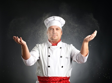 cook scatters flour on grey background