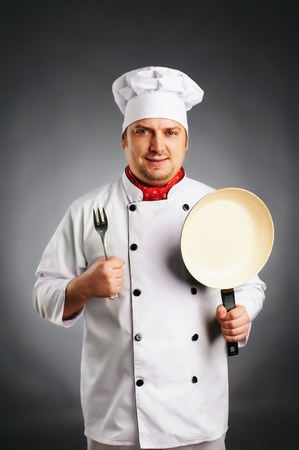 smiling cook with knife and pan in his hands on grey background