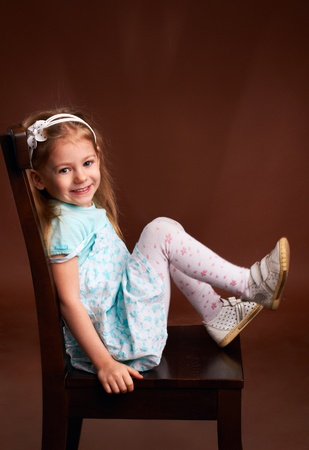 Smiling little girl sitting on a chair