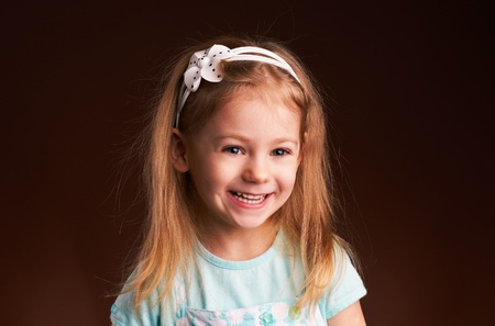 little girl smiling on a brown background Stock Photo