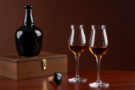 composition with  bottle and glass of brandy on brown background Stock Photo