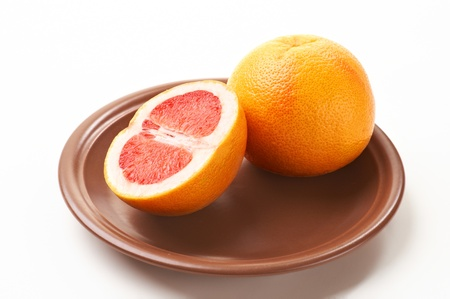cut and whole grapefruits on a ceramic plate Stock Photo