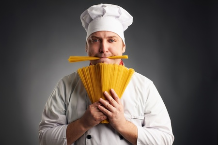 funny cook with spaghetti in his mouth on grey background Stock Photo