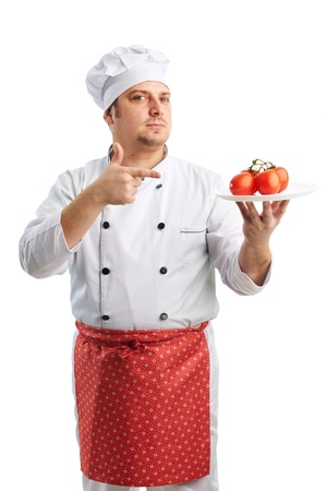 attractive chef in uniform shows tomatoes photo