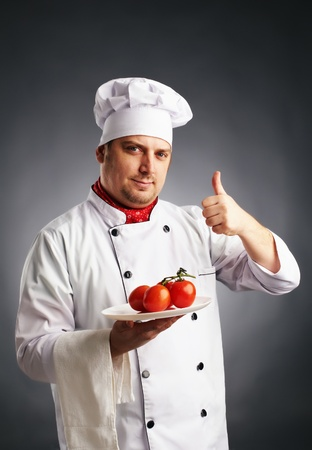 attractive cook in uniform with tomatos give the thumbs up photo