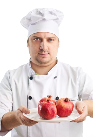 cook in uniform with pomegranates, selective focus Stock Photo