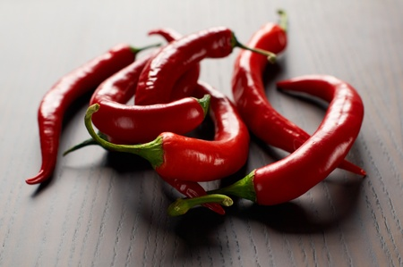 red chili peppers on a wooden table with selective focus