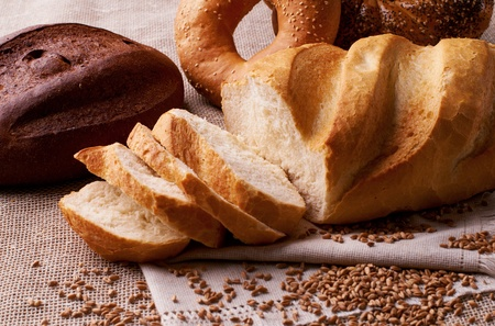 cut  baked bread with wheat on the tablecloth