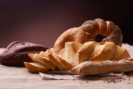 cut and whole baked bread with wheat on the tablecloth Stock Photo