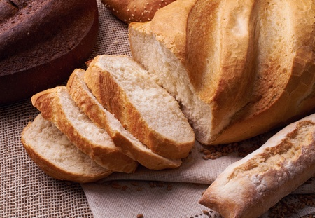 Cut fresh bread on the tablecloth Stock Photo