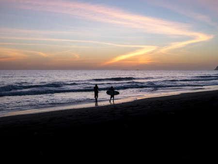 surfers: Surfers walks along the beach in Costa Rica