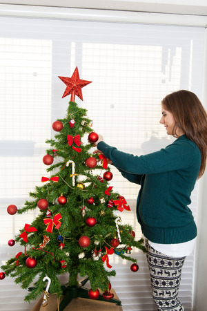30 35 years: Woman pregnant decorating a christmas tree