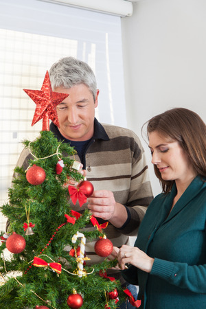 35 40 years old: Couple decorating christmas tree