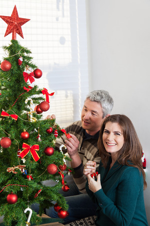 35 40 years old: Husband and wife decorating christmas tree
