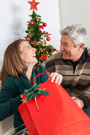 35 to 40 years old: Woman opening the gift and laughing