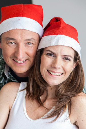 35 to 40 years old: Happy couple in christmas hats