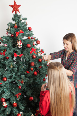 8 10 years: Woman and her son decorating the christmas tree Stock Photo