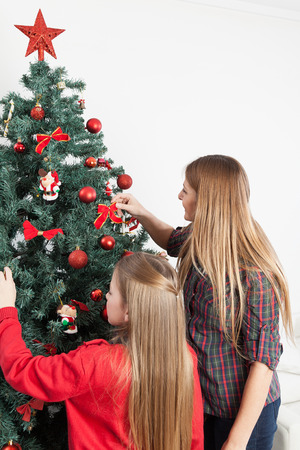 8 10 years: Mother and daughter preparing the christmas tree