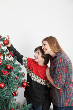 Mom with her son putting ornaments on the christmas tree photo