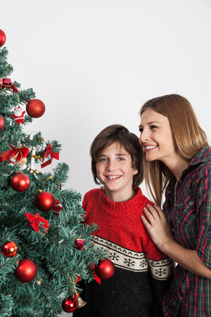 boy 12 year old: Happy mom and son beside the christmas tree