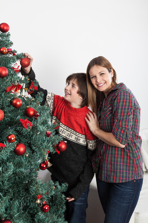 Boy and his mom smiling beside the christmas tree photo