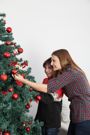 boy 12 year old: Mom with her son decorating the christmas tree Stock Photo