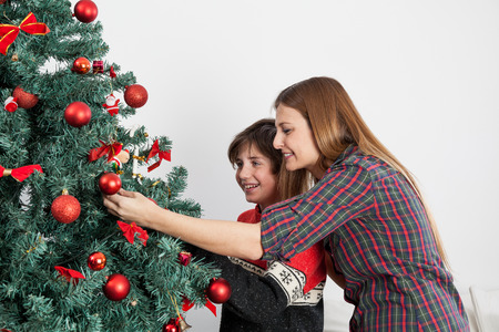 boy 12 year old: Happy mom and son decortating the christmas tree Stock Photo