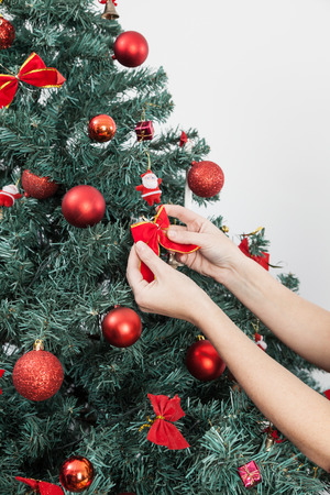 30 35 years women: Happy woman putting a bow in the christmas tree