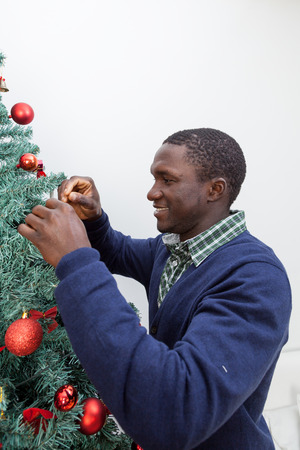 30 to 35: Black man decorating the Christmas tree