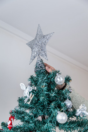 35 40 years old: Man putting the star of christmas tree Stock Photo