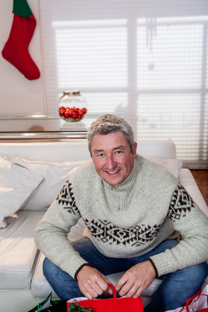 35 years old man: Man sitting in his couch preparing de gifts christmas