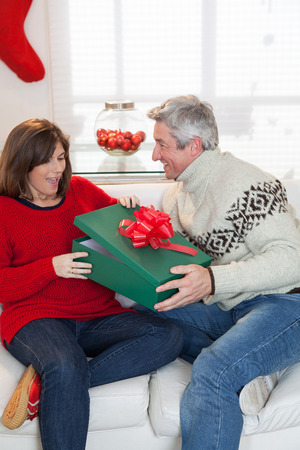 daugther: Woman opening the gift that gives her husband