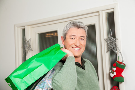 35 40 years old: Happy man holding a gift bag
