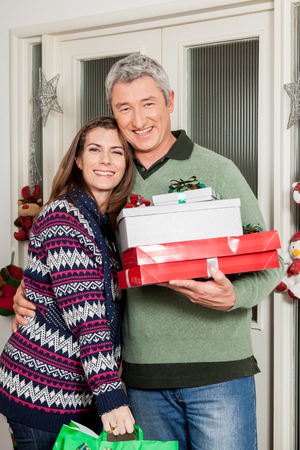 35 40 years old: Happy couple holding a christmas gifts
