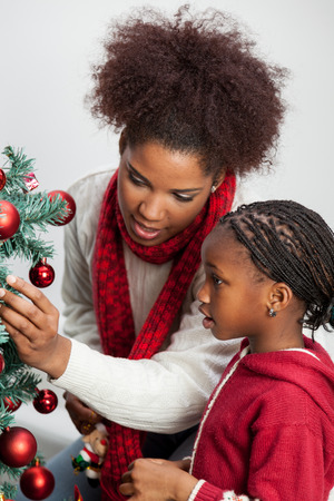 family at home: Mother and daughter decorating Christmas tree Stock Photo