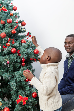 Boy decorating the christmas tree with his father
