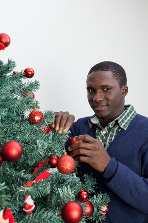 30 to 35: Man decorating the Christmas tree and looking at camera