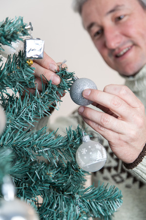 35 years old man: Man decorating the christmas tree