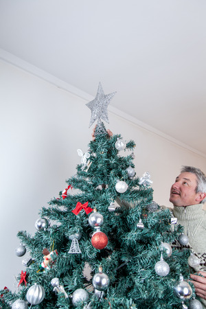 35 40 years old: Man placing the star on the christmas tree