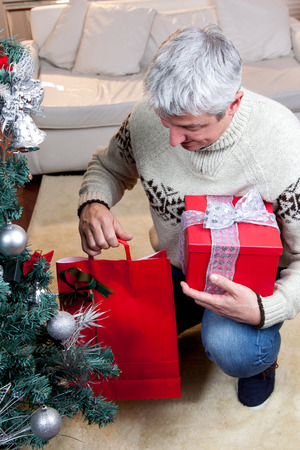 35 to 40 years old: Man putting the gift under the christmas tree Stock Photo